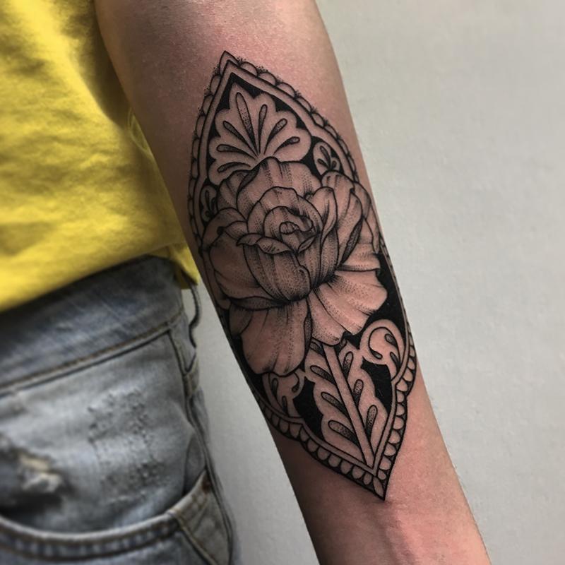 intricate floral blackwork tattoo on forearm